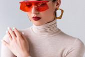 elegantní dívka v červené sluneční brýle dotýkat rameno při pózování izolované na šedé