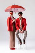 volle Länge Ansicht der trendigen Frau mit Regenschirm in der Nähe stilvolle Mann sitzt auf Hocker auf grau