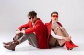 módní pár v červených blejzrech a slunečních brýlích sedí na podlaze, zatímco pózuje na šedé