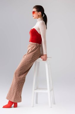 Side view of fashionable girl in beige trousers and red corset on turtleneck leaning on stool on grey stock vector