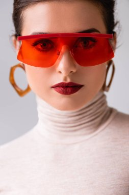 Portrait of beautiful woman in red sunglasses looking at camera isolated on grey stock vector