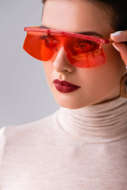 Portrait of attractive girl in red sunglasses looking away and touching frames isolated on grey stock vector