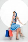 Trendy girl in gloves and sunglasses holding blue and red shopping bags while sitting in circle on white background
