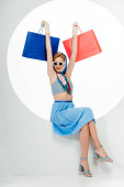 Cheerful stylish woman holding blue and red shopping bags in circle on white background