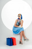 Fashionable girl in sunglasses and headscarf sitting in circle near shopping bags on white background