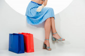 Cropped view of stylish woman sitting in circle near red and blue shopping bags on white background