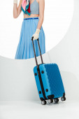 Oříznutý pohled stylové dívky držící modrý kufr za kulaté díry na bílém pozadí