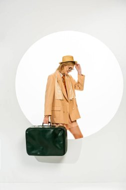 Stylish woman smiling while holding green travel bag near circle on white background stock vector