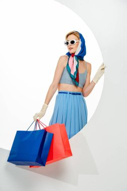 Fashionable woman in blue skirt and accessories holding shopping bags near circle on white background stock vector