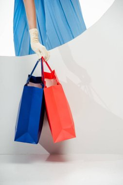 Cropped view of stylish woman in glove holding red and blue shopping bags near round hole on white background stock vector