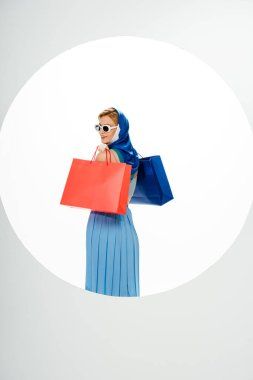 Back view of smiling woman in headscarf and sunglasses holding red and blue shopping bags behind circle on white background stock vector