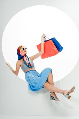 Fashionable woman in sunglasses posing while blue and red shopping bags in circle on white background stock vector