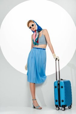 Stylish woman in sunglasses and gloves holding blue suitcase near circle on white background stock vector