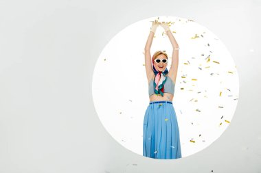 Positive girl in sunglasses standing near circle under falling confetti on white background stock vector