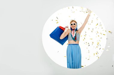 Smiling woman in sunglasses holding colorful shopping bags under falling confetti near circle on white background stock vector