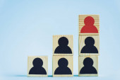 pyramid of wooden blocks with black and red human icons on blue background, leadership concept