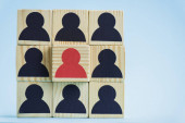 Photo square of wooden blocks with black and red human icons on blue background, leadership concept