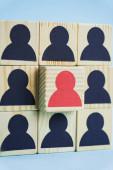 čtverec dřevěných bloků s černými a červenými lidskými ikonami na modrém pozadí, koncept vedení
