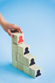 cropped view of hand touching pyramid of wooden blocks with black and red human icons on blue background, leadership concept