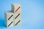 wooden blocks with black and red arrows on blue background, leadership concept