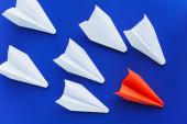 horní pohled na bílá a červená papírová letadla na modrém pozadí, koncept vedení
