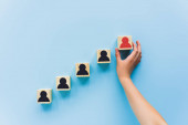 partial view of hand and wooden blocks with black and red human icons on blue background, leadership concept