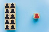 Photo top view of wooden blocks with black and red human icons on blue background, leadership concept