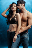 Handsome muscular man hugging sexy girlfriend in bra and jeans on black background with smoke