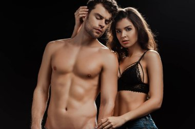 Sexy woman looking at camera while touching shirtless boyfriend isolated on black stock vector