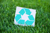 Selective focus of card with recycle sign on grass outdoors, ecology concept