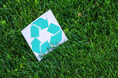 High angle view of card with recycle symbol on green grass outdoors, ecology concept