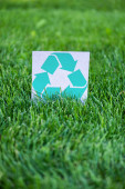 Selective focus of card with recycle sign on green grass, ecology concept