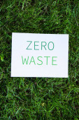 Top view of card with zero waste words on grass, ecology concept