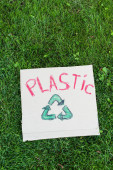 Top view of placard with plastic lettering and recycle sign on grass, ecology concept