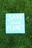Top view of placard with save our planet bettering on grass, ökológia koncepció