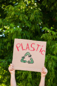 Cropped view of man holding placard with plastic lettering and recycle sign with trees at background, ecology concept