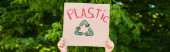 Panoramic crop of man holding placard with recycle sign and plastic lettering with trees at background, ecology concept
