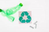Horní pohled na kartu s recyklační značkou v blízkosti zmačkaných plastových lahví a akumulátorů na bílém pozadí, koncept ekologie