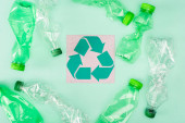 Top view of card with recycle sign near crumpled bottles on green background, ecology concept