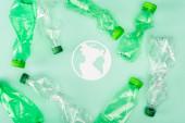 Horní pohled na papírovou planetu poblíž zmačkaných plastových lahví na zeleném povrchu, koncept ekologie