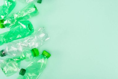 Top view of crumpled plastic bottles on green background with copy space, ecology concept stock vector