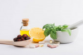 green leaves in mortar, berries and lemon near pills on white background, naturopathy concept
