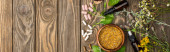 top view of pills, green herbs and wildflowers on wooden surface, naturopathy concept