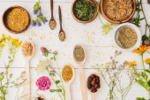 top view of herbs in spoons and bowls near flowers on white wooden background, naturopathy concept