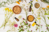 top view of herbs in bowls near flowers and bottles on white wooden background, naturopathy concept