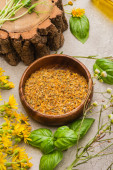 Fotografie bowl with herb, wildflowers, green leaves on concrete background, naturopathy concept