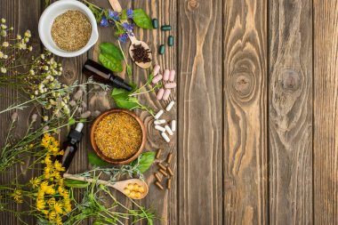 top view of pills in spoons, green herbs and wildflowers on wooden surface, naturopathy concept