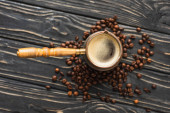 top view of cezve with coffee on coffee beans on wooden surface