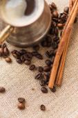zblízka pohled na cezve s kávou v blízkosti skořicových tyčinek a kávových zrn na pytlovině