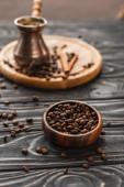 selektivní zaměření kávových zrn v misce a cezve na dřevěném povrchu